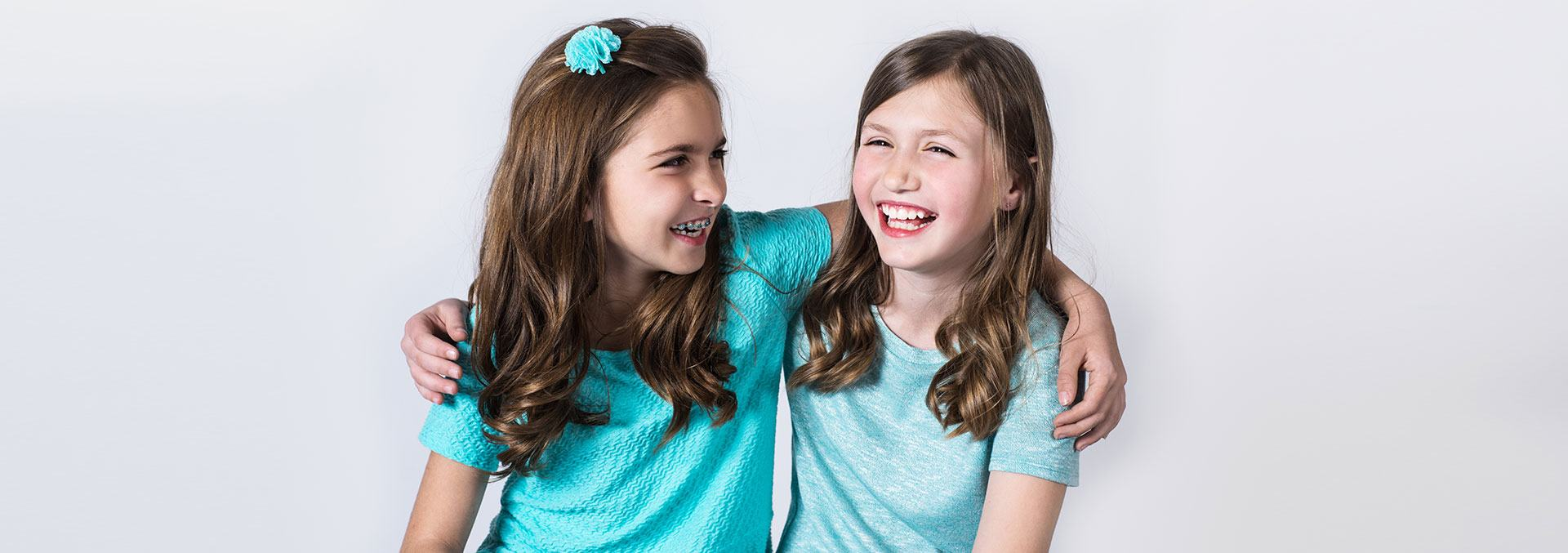 two young girls with their arms around each other laughing